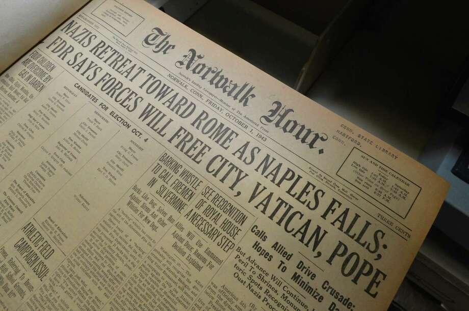 Oct. 1, 1943, edition of The Norwalk Hour (l.), with World War II headlines. The flag being retired, below. Photo: Alex Von Kleydorff / Hearst Connecticut Media / Norwalk Hour
