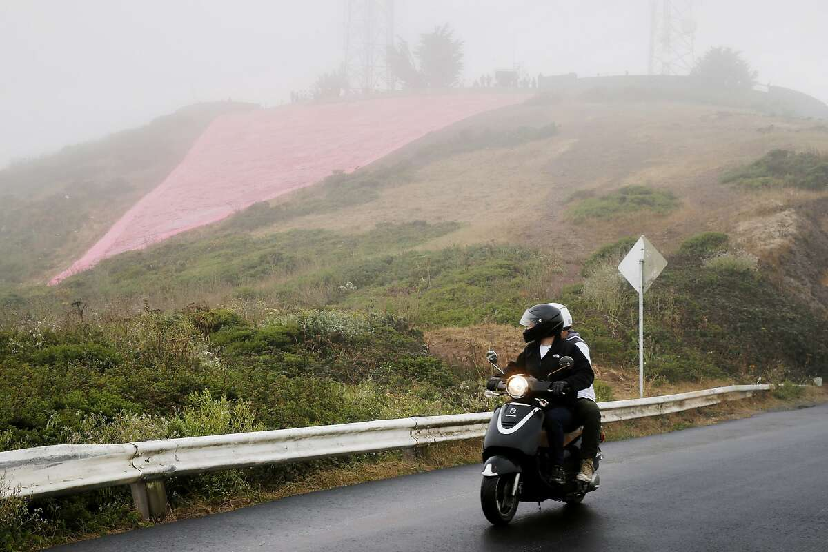 Lucas Ewalt drives down the hill with Ronnie Wrobel to get a better view of the Pink Triangle at Twin Peaks on Saturday, June 24, 2017, in San Francisco, Calif. The Pink Triangle is a remembrance of the years of discrimination and physical attacks on the LGBT community. The two helped with the installation.