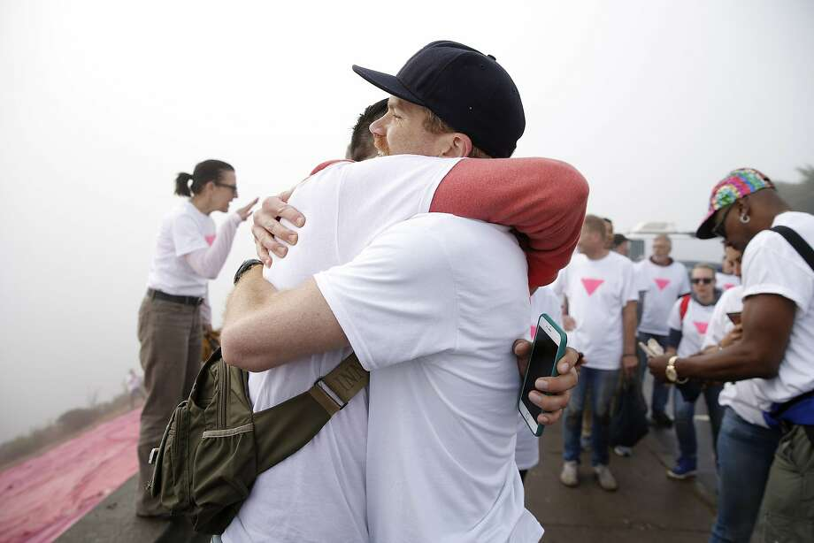 Oscar Padilla (left) embraces Todd Iceton after installing the pink triangle for Pride weekend in San Francisco. Photo: Santiago Mejia, The Chronicle