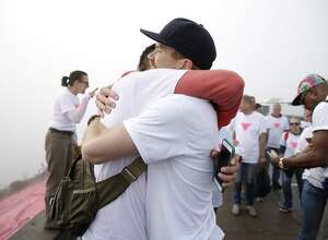 From center left: Oscar Padilla embraces Todd Iceton after installing the Pink Triangle at Twin Peaks on Saturday, June 24, 2017, in San Francisco, Calif. The Pink Triangle is a remembrance of the years of discrimination and physical attacks on the LGBT community.