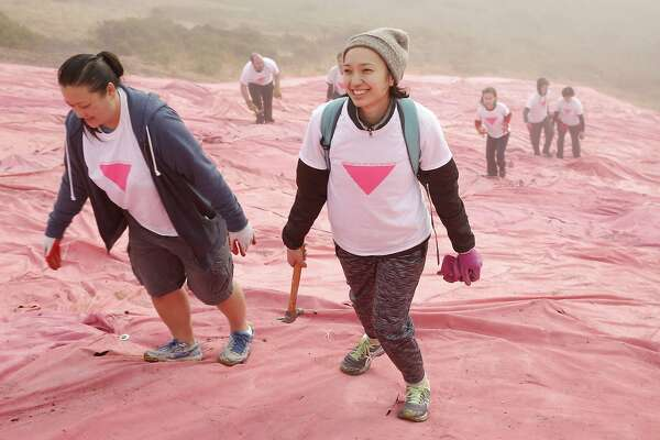 From left: Thao Nguyen and her sister Amy Herbertson walk back up the hill after helping install the Pink Triangle at Twin Peaks on Saturday, June 24, 2017, in San Francisco, Calif. The Pink Triangle is a remembrance of the years of discrimination and physical attacks on the LGBT community.