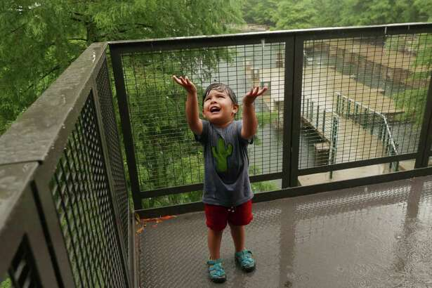 """Three-year-old Isaac Villarreal shouts """"¡Lluvia! Lluvia!"""" which is the Spanish word for rain, during a downpour as he and his family visit the Pearl complex on Saturday afternoon, June 24, 2017."""