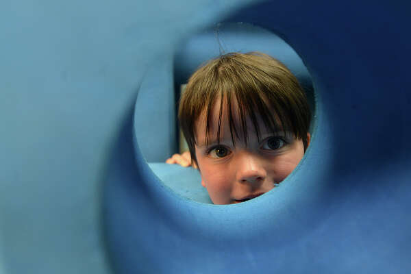 Benjamin David Perkinz, 3, peers out from a hole in a foam building block as he and other children play inside the Imagination Playground at the Beaumont Children's Museum. Perkinz and family were among the many who filled the museum for its Lego Day event and other activities Saturday. Photo taken Saturday, June 24, 2017 Kim Brent/The Enterprise