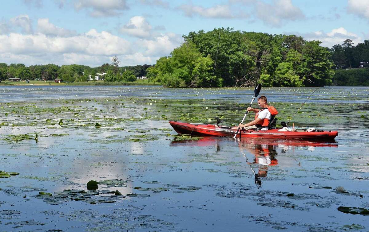 Ben Sledziewski of Scotia kayaks along the shore of Collins Lake to try his luck on the opening day of bass fishing season Saturday June 24, 2017 in Scotia, NY. (John Carl D'Annibale / Times Union)