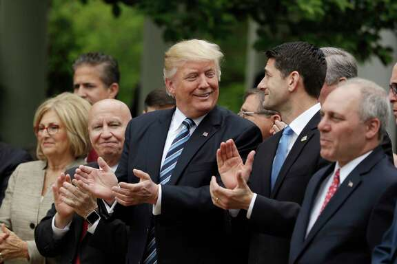 President Donald Trump, flanked by House Ways and Means Committee Chairman Rep. Kevin Brady, R-Texas, and House Speaker Paul Ryan of Wis. applaud in the Rose Garden of the White House in Washington, Thursday, May 4, 2017, after the House pushed through a health care bill. (AP Photo/Evan Vucci)