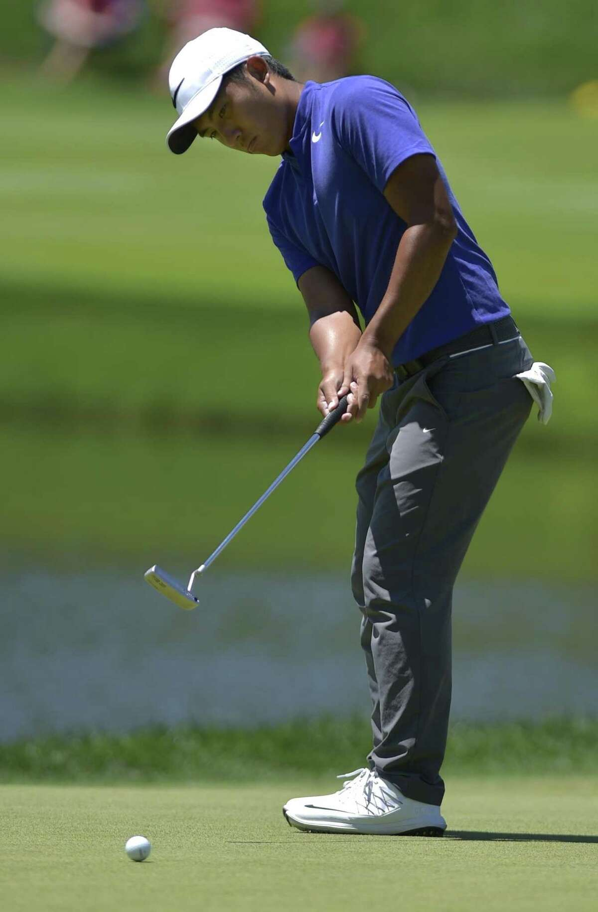 C.T. Pan putts on the 17th green during the third round of the Travelers Championship golf tournament at TPC River Highlands on Saturday, June 24, 2017, in Cromwell, Conn. (Brad Horrigan/Hartford Courant via AP)