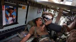 Air Force Cpt. Shad Magann, SSg. Travis Crosby, and Spc Bryan Slick sleep in the back of an armored vehicle after an overnight and early morning fight for control of Saddam International Airport Friday, April 4, 2003 in Iraq. BAHRAM MARK SOBHANI/STAFF
