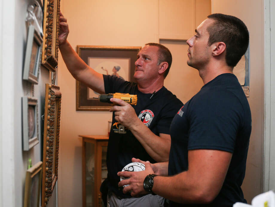 Champions E.S.D. Commissioner David Parker, left, and Needham firefighter Cody McDougald, right, install smoke detectors in a Tamina resident's home on Saturday, June 24, 2017. Photo: Michael Minasi, Staff Photographer / © 2017 Houston Chronicle
