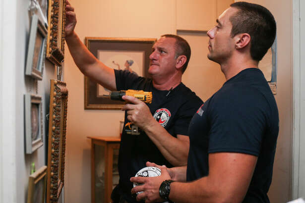 Champions E.S.D. Commissioner David Parker, left, and Needham firefighter Cody McDougald, right, install smoke detectors in a Tamina resident's home on Saturday, June 24, 2017.