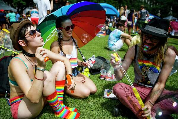 Ruthie Ocean, left, blows bubbles as she sits with Sarah Elaine, center, and Stephen Ferguson during the Houston Pride Festival Saturday, June 24, 2017 in Houston.
