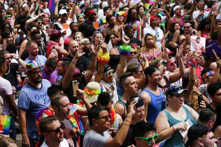 Revelers listen to a concert on the steps of City Hall during the Houston Pride Festival Saturday.