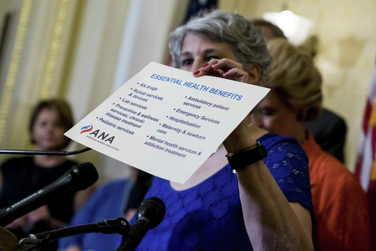 American Nurses Association President Pamela Cipriano holds up a list of essential health benefits as she discusses the effects of the proposed Republican healthcare legislation on families at a news conference with Democratic senators on Capitol Hill in Washington on Thursday. Senate Republicans would cut Medicaid, end penalties for people not buying insurance and erase a raft of tax increases.