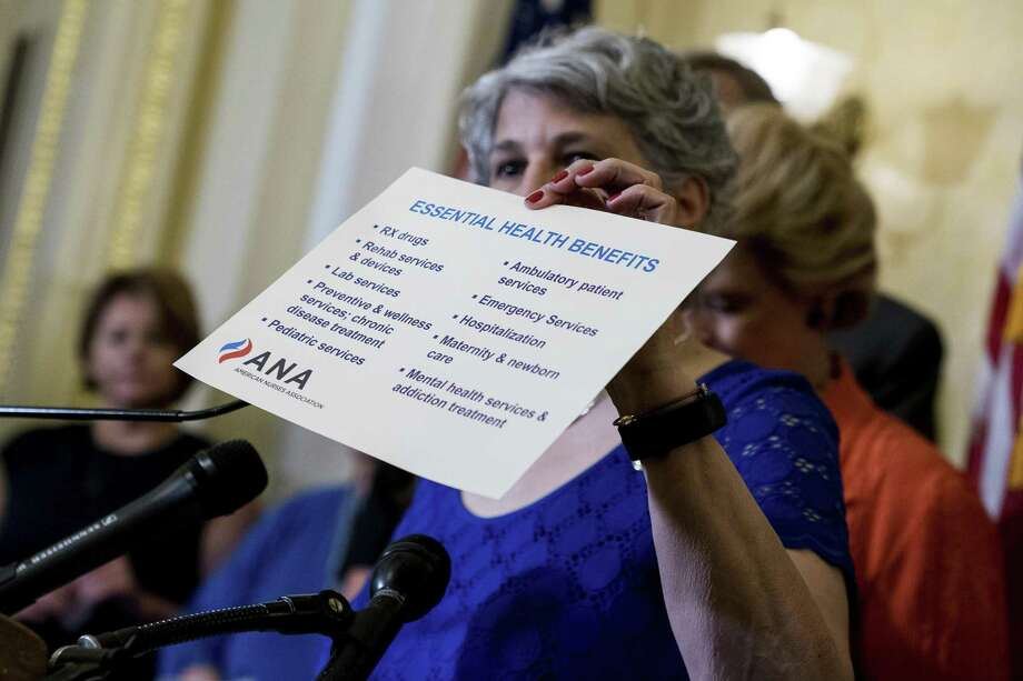 American Nurses Association President Pamela Cipriano holds up a list of essential health benefits as she discusses the effects of the proposed Republican healthcare legislation on families at a news conference with Democratic senators on Capitol Hill in Washington on Thursday. Senate Republicans would cut Medicaid, end penalties for people not buying insurance and erase a raft of tax increases. Photo: Andrew Harnik / Associated Press / Associated Press