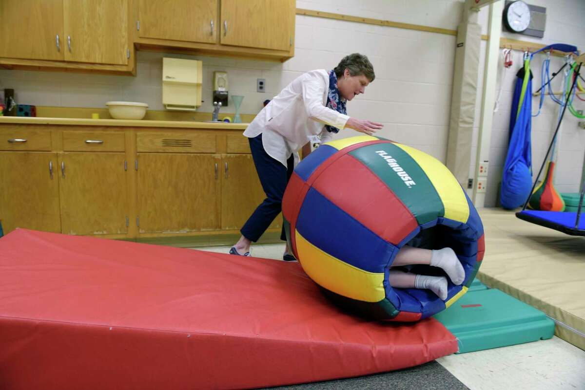 Michele Sloan, a occupational therapist for the Saratoga Springs City School District, works with a student at Greenfield Elementary School on Thursday, June 8, 2017, in Greenfield Center, N.Y. The padded barrel is used for vistibular input to promote self regulation in the student. (Paul Buckowski / Times Union)