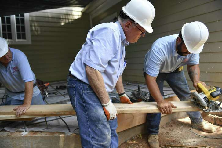 Bob Luckett, founder of Veteran's Next Mission, center, works on laying down a form as veterans Brian Mandes, Army National Guard, left, holds the lumber in place while Derek Lett, U.S. Army, right, cuts the lumber with a power saw during the construction of a home addition in Arlington, Virginia. MUST CREDIT: Photo by Ricky Carioti for The Washington Post.