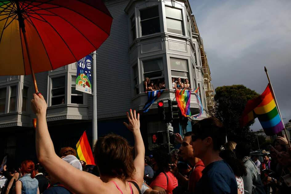 Observers cheer from a window as people walk past during the annual Dyke March that started at Mission Dolores park and snaked around the neighborhood up through the Castro and back June 24, 2017 in San Francisco, Calif.