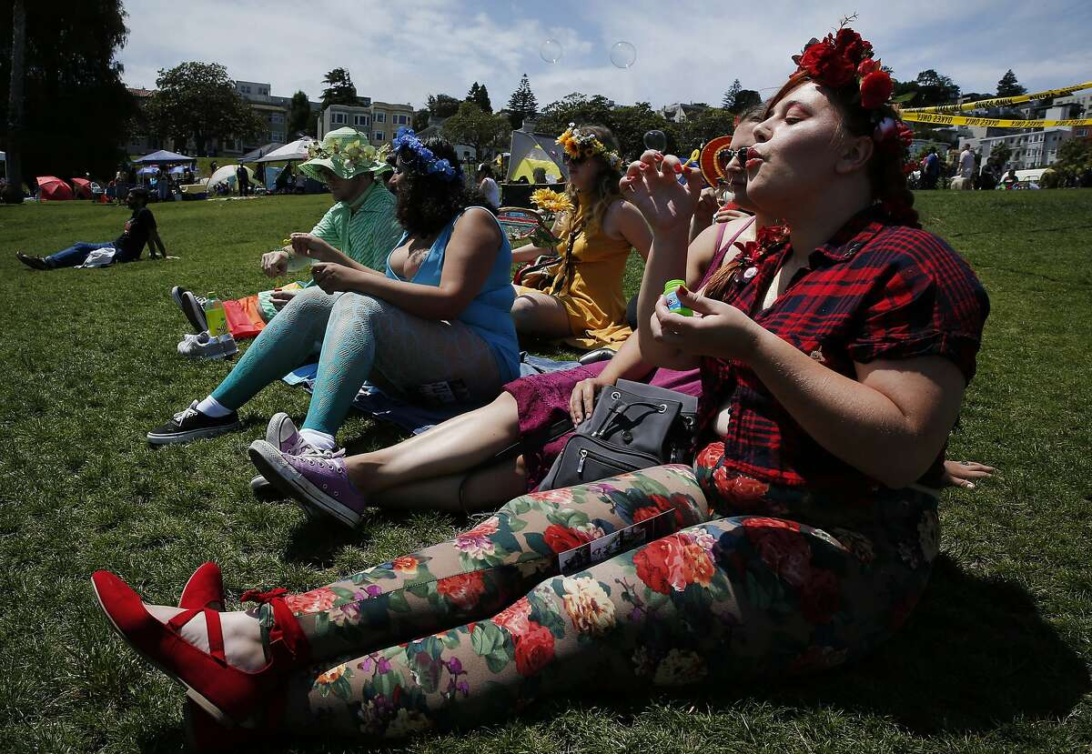 Right: Shelby Wallace blows bubbles during the 25th annual Dyke March at Dolores Park on Saturday, June 24, 2017, in San Francisco, Calif. Wallace and her friends dressed up as the colors of the rainbow flag.