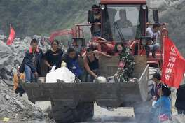 A woman griefs for her relatives as volunteers deliver supplies at the site of a landslide in Xinmo village in Maoxian County in southwestern China's Sichuan Province, Sunday, June 25, 2017. Crews searching through the rubble left by a landslide that buried a mountain village under tons of soil and rocks in southwestern China on Saturday found bodies, but more than 100 people remained missing. (AP Photo/Ng Han Guan)