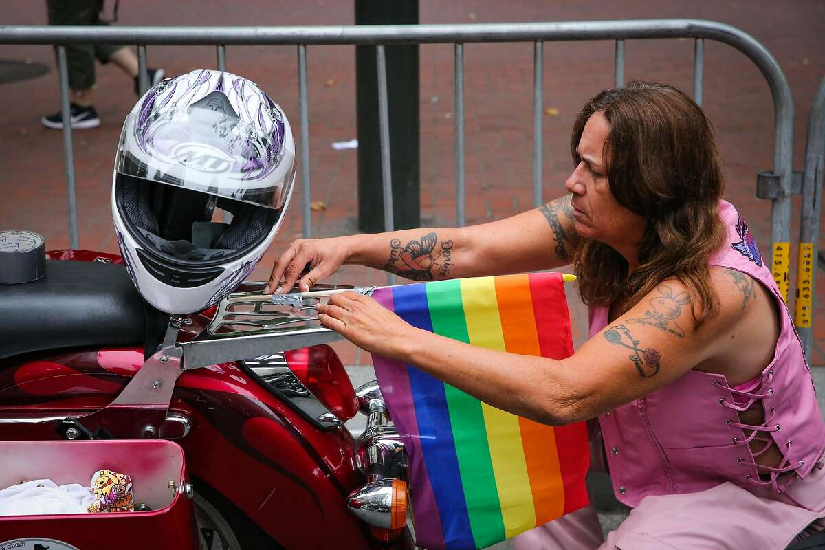 FILE - Juliana Lok adds a rainbow flag to her motorcycle ahead of the Pride Parade in San Francisco in this June 25, 2017 file photo.
