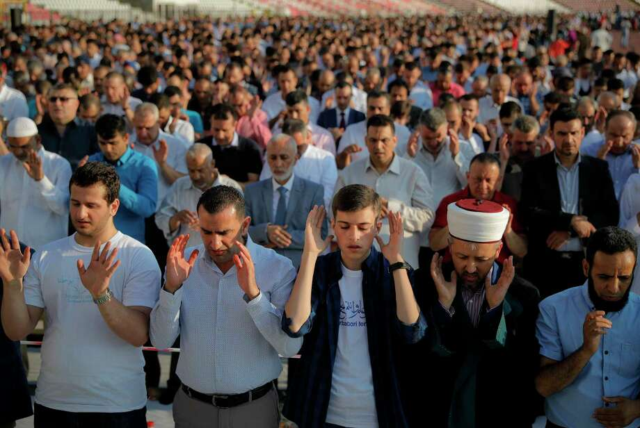 Muslims take part in Eid al-Fitr prayers in Bucharest, Romania, Sunday, June 25, 2017. Members of the Romania Muslim community joined prayers at the Dinamo stadium in the Romanian capital, in the largest Muslim public gathering of the year which marks the end of the holy fasting month of Ramadan. Photo: Vadim Ghirda, AP / Copyright 2017 The Associated Press. All rights reserved.