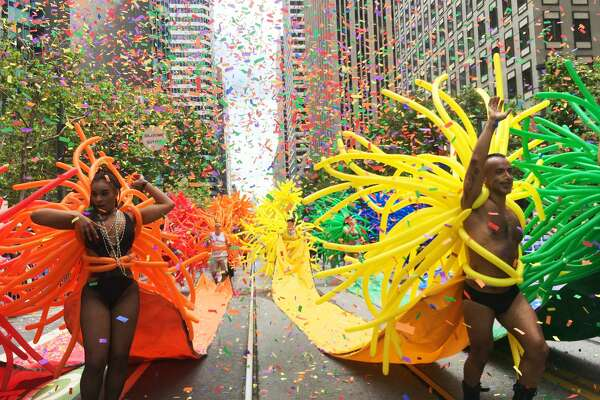 Dancers head down Market Street in a shower of confetti and balloons as they march in the 2017 Pride Parade.