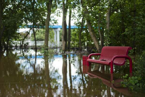 Floodwater surrounds a park bench behind Riverside Place Senior Living Community on Sunday, June 25, 2017.