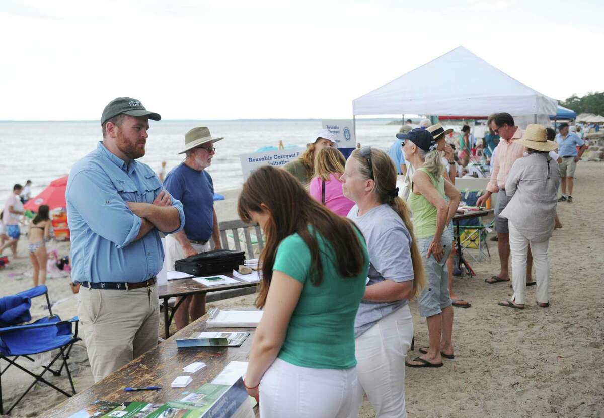 Folks browse various booths along the beach during the