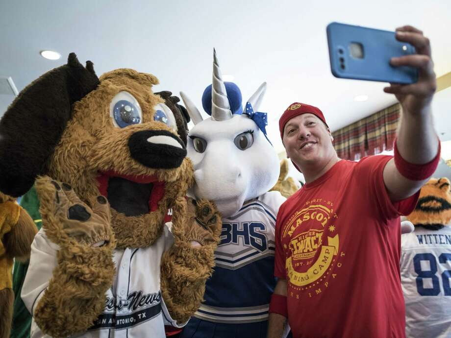 Jerome Bartlett, right, practices taking a selfie with Emily Simmons, 13, left, Marshall Middle School mascot, and Abbie Tate, 15, Unis the Unicorn from New Braunfels High School, during the Mascot training camp put on by Higher Impact Entertainment at the Crockett Hotel in San Antonio, TX on Saturday, June 24, 2017. The one-day camp that is in its sixth year, teaches mascots from middle school to the professional level how to care for their costumes, interact with fans and improve their skills. The workshop is directed by Higher Impact Entertainment director Jerome Bartlett, a former mascot for the Spurs organization as a backup Coyote, T-Bone for the Rampage, and was named the 2006 National Mascot Champion. Photo: Matthew Busch, For The San Antonio Express-News / For The San Antonio Express-News / © Matthew Busch