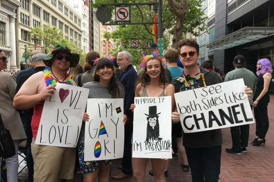 Pride attendees Max, Cina, Fiona and Conner (surnames not given) display their Pride signs on June 25, 2017. The second-from-right sign is a reference to  The Babadook , a 2014 horror film whose titular monster has become an ironic LGBT mascot in some online circles.