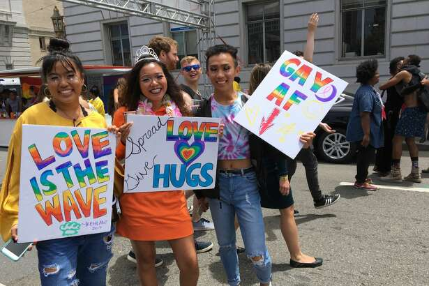 Pride attendees and parade participants show off their signs on June 25, 2017.
