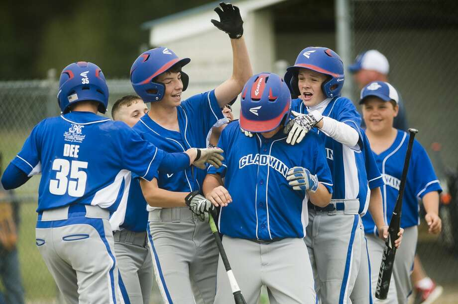 Gladwin players celebrate with Lincoln McKinnon, center, after McKinnon scored a run during their semi-finals game against Midland Northeast during the 6th Annual Gladwin Little League Jeffrey J. Werda Memorial All-Star Tournament on Sunday, June 25 in Gladwin. Photo: (Katy Kildee/kkildee@mdn.net)