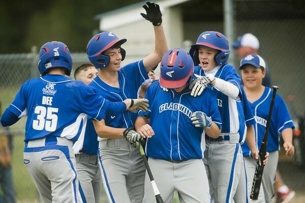 Gladwin players celebrate with Lincoln McKinnon, center, after McKinnon scored a run during their semi-finals game against Midland Northeast during the 6​th​ Annual Gladwin Little League Jeffrey J. Werda Memorial All-Star Tournament on Sunday, June 25 in Gladwin.