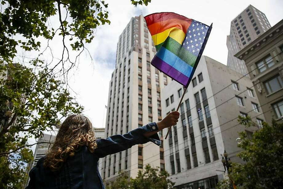 Parker Mead sits on her father's shoulders and waves a rainbow colored American flag during the Pride Parade in San Francisco on Sunday. Photo: Nicole Boliaux, The Chronicle