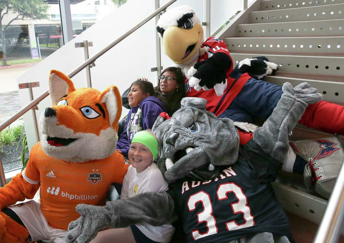 Mia Spargo, 10, front, Bryssa Luna, 10, center, and Brianna Luna, right, 15, take a photo with Diesel the official mascot of Houston Dynamo and Dash, Spike the mascot of Austin High School, and Slapshot the official mascot of the Washington Capitals at Breakfast with Mascots at Queensbury Theatre Sunday, June 25, 2017, in Houston. Mia, a brain cancer survivor, and Bryssa, who has retinoblastoma, became friends at Camp Periwinkle for Children with Cance and have been supporting each other and fighting cancer together.