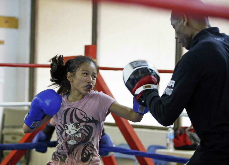 Yemila Tobias work out with coach Jeff Mays.Weighing in at 90 lbs., 12 year old Yemila Tobias is an up and coming boxer training under Jeff Mays, Army retiree and assistant coach for the Women's United States Boxing Team. She Trains at the East Side Boys and girls Club of America on 4/5/2017. Photo: Ron Cortes /Ronald Cortes / Freelance