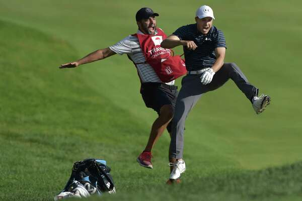 Jordan Spieth celebrates with caddie Michael Greller after Spieth holed a bunker shot on a playoff hole on the 18th hole to win the Travelers Championship Sunday in Cromwell.