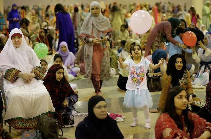 Maha Mahmood, 4, plays with a balloon before the Islamic Society of Greater Houston's Eid Al-Fitr prayer at NRG Center  Sunday, June 25, 2017, in Houston. Eid al-Fitr is the festive holiday that marks the end of Ramadan, the Islamic holy month of fasting. ( Melissa Phillip / Houston Chronicle )