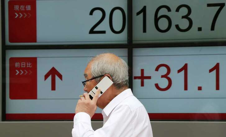 A man walks in front of an electronic stock board of a securities firm in Tokyo, Monday, June 26, 2017.  Asian markets rose Monday after Wall Street rebounded from losses to end the week higher on stronger oil and natural gas prices. (AP Photo/Koji Sasahara)