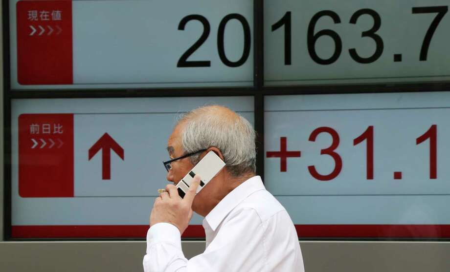 A man walks in front of an electronic stock board of a securities firm in Tokyo, Monday, June 26, 2017.  Asian markets rose Monday after Wall Street rebounded from losses to end the week higher on stronger oil and natural gas prices. (AP Photo/Koji Sasahara) Photo: Koji Sasahara, Associated Press / Copyright 2017 The Associated Press. All rights reserved.