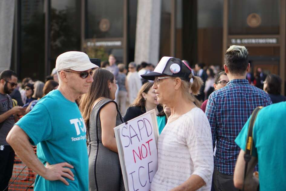 "Protestor Ann Megee, with The UnSilent Majority, holds a sign in protest of Senate Bill 4 as she speaks with Mike Crow, a protestor with Texas Organizing Project. ""(Local police) are being asked to be federal agents with no compensation,"" Megee said. ""Greg Abbott is a little out of line on this one."""