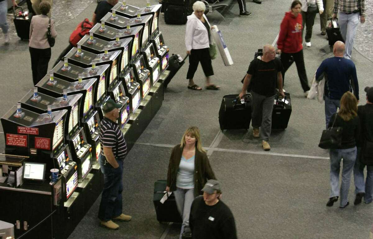 Travelers pass by slot machines in the baggage pick-up area at McCarran International Airport in Las Vegas.