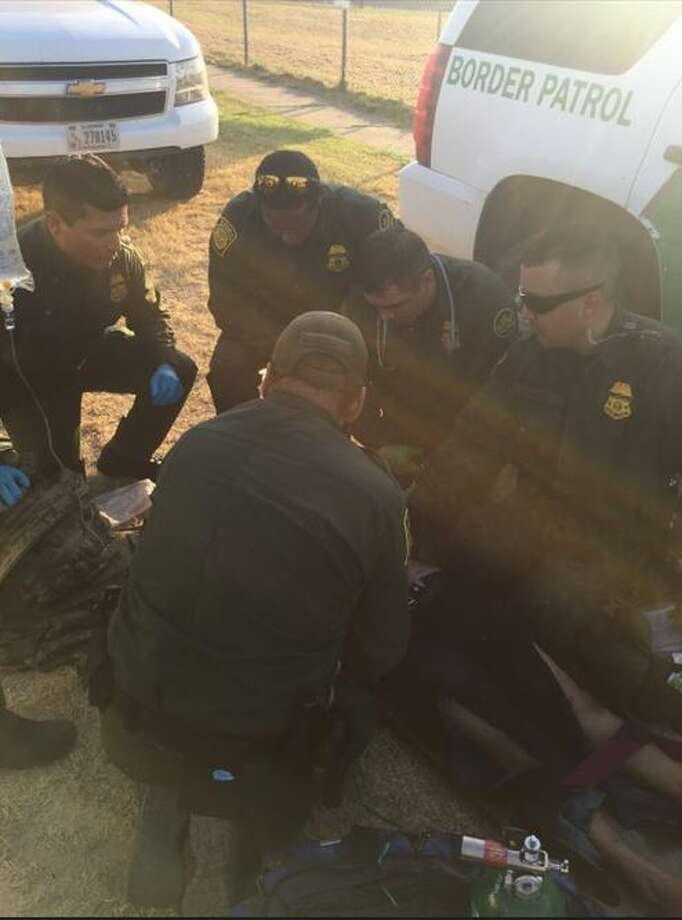 Border Patrol agents attend to a female immigrant who showed signs of suffering from a heat stoke.  Photo: Courtesy