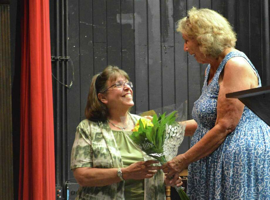 Cheryl Petrone of Norwalk, left, receives a gift for her service from outgoing President Sheri Dean at the Town Players of New Canaan's annual business meeting and patio party, Sunday, June 25, 2017, at the Powerhouse Performing Arts Center in New Canaan, Conn. Photo: Jarret Liotta / For Hearst Connecticut Media / New Canaan News Freelance