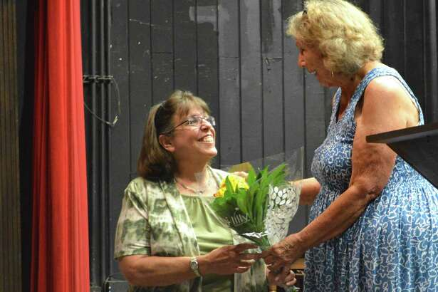 Cheryl Petrone of Norwalk, left, receives a gift for her service from outgoing President Sheri Dean at the Town Players of New Canaan's annual business meeting and patio party, Sunday, June 25, 2017, at the Powerhouse Performing Arts Center in New Canaan, Conn.