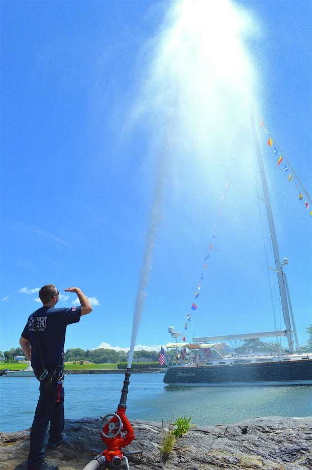 "Firefighter Jay Hayes oversees the firehose as the ship ""Beguine"" passes through the harbor during the annual Blessing of the Fleet in Southport Harbor, Saturday, June 24, 2017, in Fairfield, Conn. Photo: Jarret Liotta / For Hearst Connecticut Media / Fairfield Citizen News Freelance"