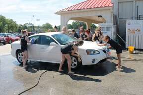 Members of the Edwardsville High School Dance Team wash a car Saturday during a fundraiser at Joe's Market Basket. Next week, the dance team will be working with the Main Street Community Center to help deliver meals.