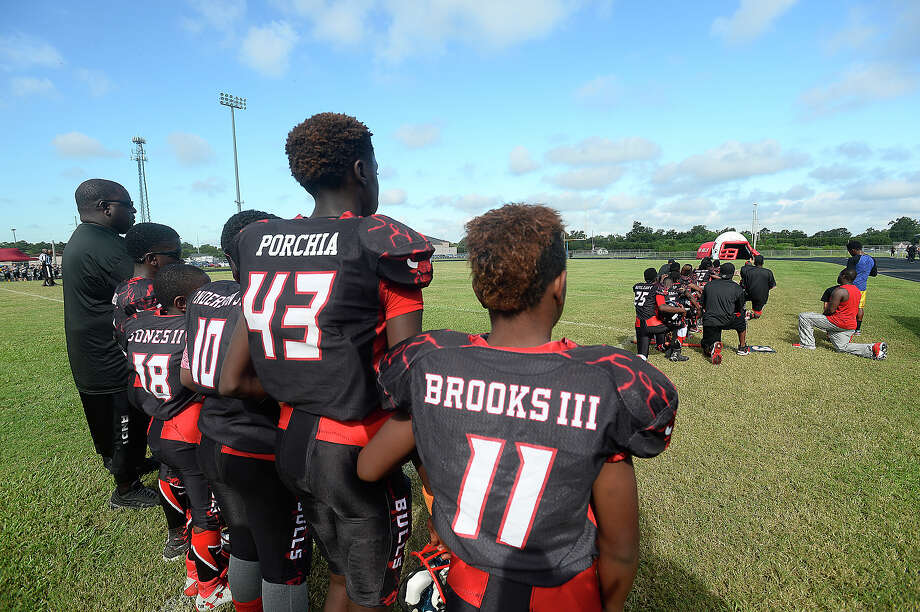 Some members of the Beaumont Bulls youth football team and coaches kneel while others stand during the playing of the National Anthem prior to their home game Saturday. The team has gotten national attention after choosing to kneel in protest of social injustice at their game last week. After receiving numerous negative comments, including threats of violence aimed at both the 11 - 12-year-old players as well as coaches and parents, questions arose as to whether their protest would continue, and what negative actions may be taken by board members of the Bulls football program. Ultimately, no action was immediately taken against those players who chose to kneel, and the game continued as scheduled. Photo taken Saturday, September 17, 2016 Kim Brent/The Enterprise Photo: Kim Brent / Beaumont Enterprise