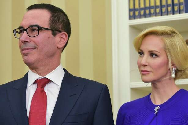 Steven Mnuchin (L) and his financee Louise Linton watch as US President Donald Trump speaks during Mnuchin's swearing-in ceremony as the next treasury secretary in the Oval Office of the White House on February 13, 2017 in Washington, DC. / AFP / MANDEL NGAN        (Photo credit should read MANDEL NGAN/AFP/Getty Images)