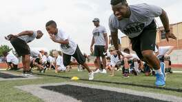 Sam Draper (center), 10, takes off on a 40-yard dash with Los Angeles Rams running back Malcolm Brown (right) at the Malcolm Brown Youth Football Camp on June 24, 2017. Brown, a Steele and UT alum, and other NFL and college players taught leadership and football skills to kids ages 6-13 during the camp at Steele High School.