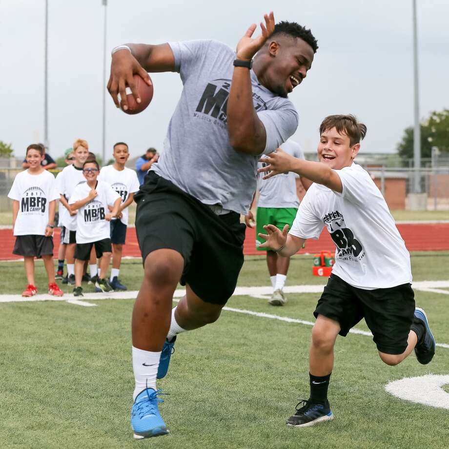 Tyler Drake, 10, tries to catch Malcolm Brown in a running back drill at the Malcom Brown Youth Football Camp where the Los Angeles Rams running back and other NFL and college players taught leadership and football skills to kids ages 6-13 at Steele High School on Saturday, June 24, 2017. Photo: Marvin Pfeiffer / San Antonio Express-News / Express-News 2017